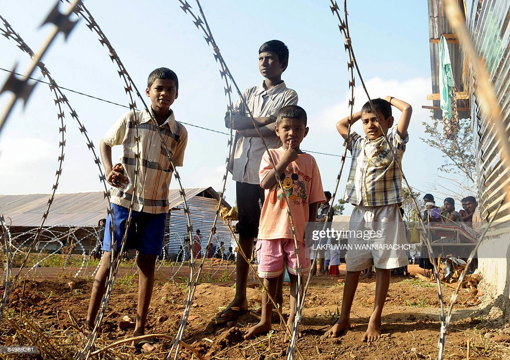 Tamil children look on at a shelter for war-displaced Tamils in Vavuniya on February 23, 2009 . Over 35,000 Tamil civilians have escaped from the conflict zone and sought shelter with government forces. International rights groups have accuse the authorities of holding the displaced civilians in prison-like conditions, a charge denie by the security forces. AFP PHOTO/Lakruwan WANNIARACHCHI