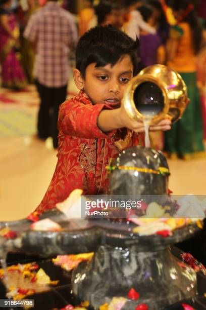 Tamil Hindu boy offers prayers by pouring milk over a Shiva Lingam during the Maha Shivratri festival at a Tamil Hindu temple in Ontario Canada on...
