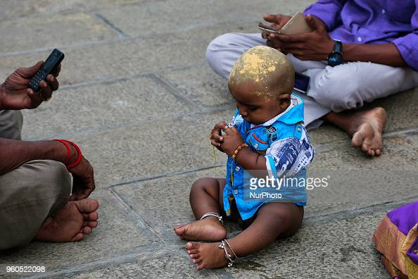 Tamil Hindu child rests after prayers at the Palani Arulmigu Shri