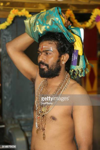 Tamil Hindu devotee carrying a coconut filled with ghee on his head to be offered to Swamy Ayyappa as part of special rituals during the 41day...