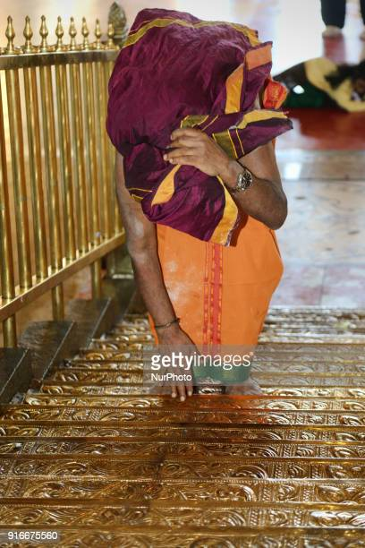 Tamil Hindu devotee climbs the pathinettaam padi while they carrying a coconut filled with ghee to be offered to Swamy Ayyappa as part of special...
