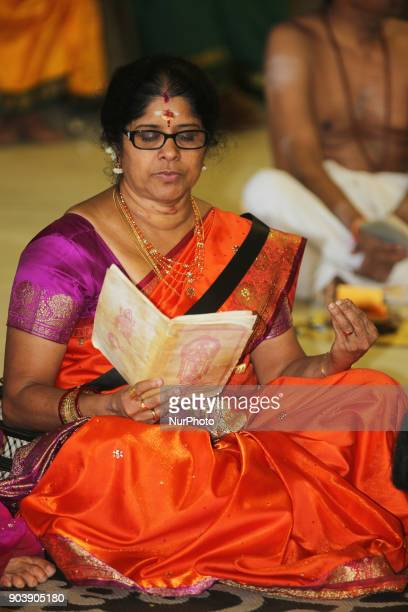 Tamil Hindu devotee reads prayers from a small prayer book as she meditates during the Theertham Thiruvizha Festival at a Tamil Hindu temple in...