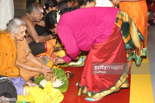Tamil Hindu devotees fill coconuts with ghee to be offered to Swamy Ayyappa as part of special rituals during the 41day Ayyappa Vratham at a Tamil...