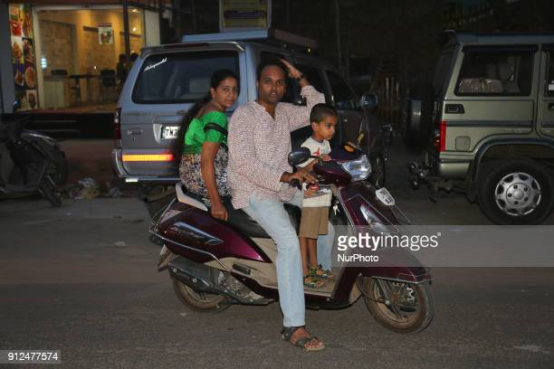 Tamil Hindu family arrives on a scooter to offer night prayers at the Nataraja Temple complex in Chidambaram Tamil Nadu India The Chidambaram...