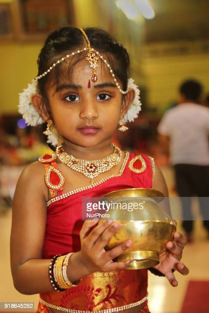 Tamil Hindu girl holds a brass pot containing milk that she waits to pour over a Shiva Lingam during the Maha Shivratri festival at a Tamil Hindu...