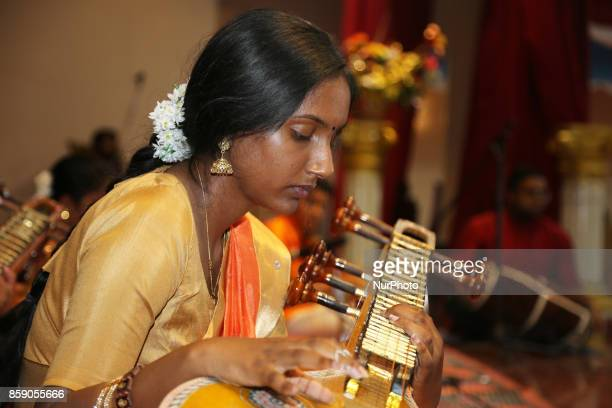 Tamil Hindu girl performs a devotional song on the veena during a Carnatic music program in Scarborough Ontario Canada