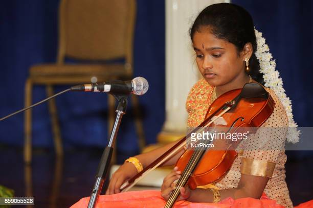 Tamil Hindu girl performs a devotional song on the violin during a Carnatic music program in Scarborough Ontario Canada