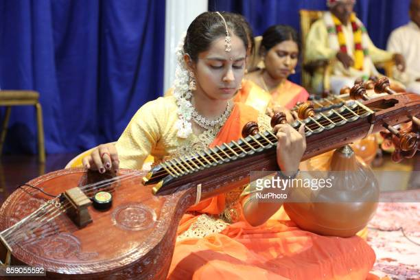 Tamil Hindu girls perform a devotional song on the veena during a Carnatic music program in Scarborough Ontario Canada