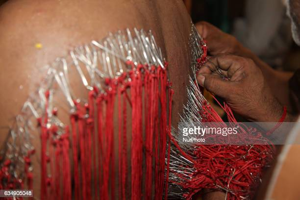 Tamil Hindu men remove hundreds of tiny hooks piercing the flesh of the back of a devotee who has completed special rituals as an act of penance...