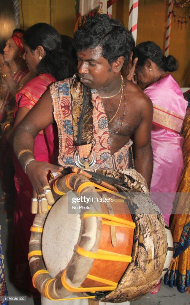 Tamil Hindu musician plays a rhythmic tune on the Thavil