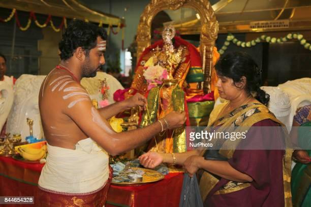 Tamil Hindu priest blesses women participating in special prayers during Varalaxmi Pooja at a Tamil Hindu temple in Toronto Ontario Canada Varalaxmi...