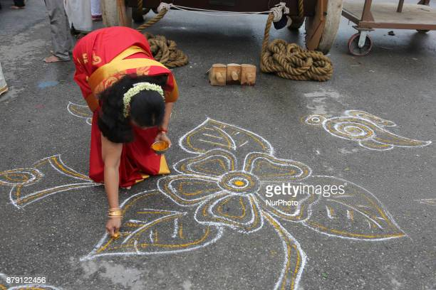 Tamil Hindu woman creates a rangoli design in front of the chariot during the Vinayagar Ther Thiruvizha Festival in Ontario Canada This festival is...