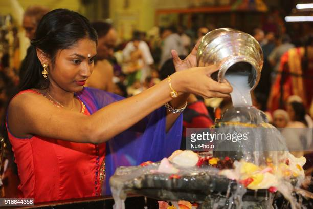 Tamil Hindu woman offers prayers by pouring milk over a Shiva Lingam during the Maha Shivratri festival at a Tamil Hindu temple in Ontario Canada on...