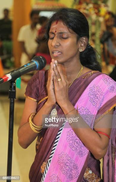 Tamil Hindu woman sings a devotional song honouring Lord Murugan during a festival at a Tamil Hindu temple in Ontario Canada