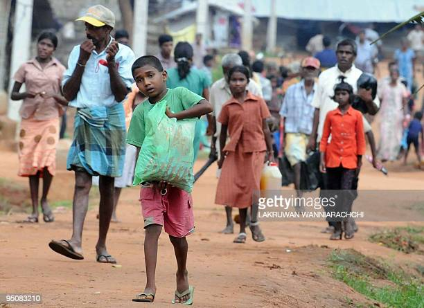 Tamil internally displaced people leave their camp with belongings in the northern town of Vavuniya on December 23 2009 Some 1000 of them were...