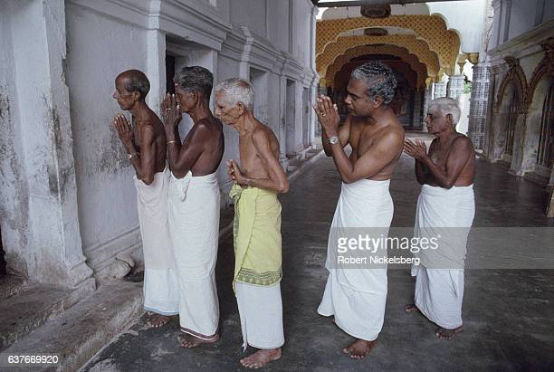 Tamil men stand outside the Nallur Hindu temple during a religious prayer ceremony February 1 1992 in Jaffna Sri Lanka