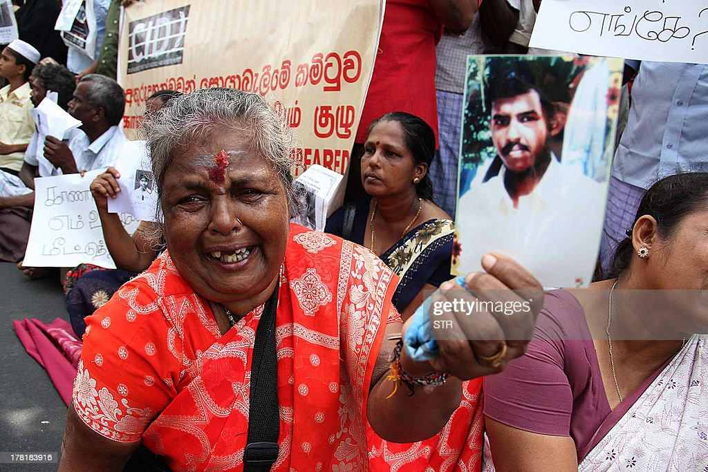 A Tamil protester holds a photograph of a missing relative at a demonstration in the northern Sri Lankan town of Jaffna on August 27, 2013 as UN Human rights chief Navy Pillay visited the area. A government census report released in February last year showed 6,350 people were reported missing in the north after the end of the fighting in the island's war in 2009 while rights groups say 'disappearances' are still a problem.