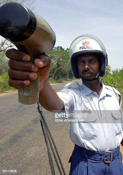 Tamil Tiger policeman uses a radar gun to trap speeding motorists 19 June 2005 near Puliyankulam along the A9 highway in northern Sri Lanka The A9...