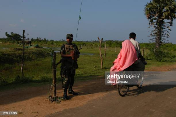 Tamil Tiger rebel wearing a camouflage outfit stands guard on Sri Lanka's northern peninsula of Jaffna The warring parties have opened a new front in...