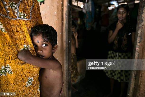 Tamil war victim Rajani grabs onto his grandmother Indra Devi outside their house in Mullaitivu Sri Lanka July 9 2013 Rajani's mother was killed...