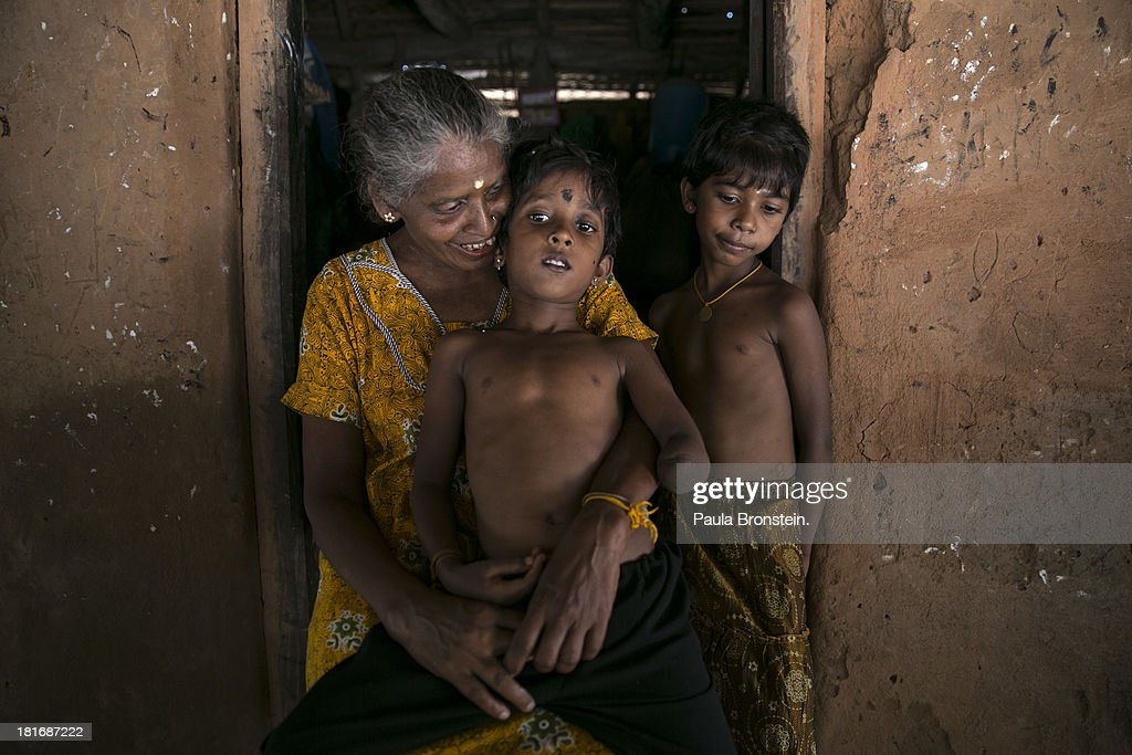 Tamil war victim Rajani,5, (center) sits on his grandmother's lap, Indra Devi, outside their house in Mullaitivu, Sri Lanka, July 9, 2013. Rajani's mother was killed while breastfeeding and shielding him during a 2009 attack in Sri Lanka's northeast. War's end has unleashed Sinhalese nationalism that has Tamils fearful of ethnic cleansing. They number around 15 per cent of the 21 million population. Sri Lanka's main Tamil party has won the first elections in the island's north after decades of ethnic war. After votes were counted, results show that the Tamil National Alliance (TNA) won 30 seats out of the 38 member council following Northern Provincial Council elections with President Mahinda Rajapaksa's coalition winning seven of the other seats.
