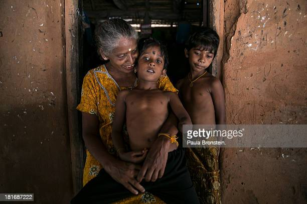 Tamil war victim Rajani sits on his grandmother's lap Indra Devi outside their house in Mullaitivu Sri Lanka July 9 2013 Rajani's mother was killed...