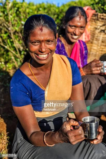 Tamil women drinking fresh tea on plantation, Ceylon