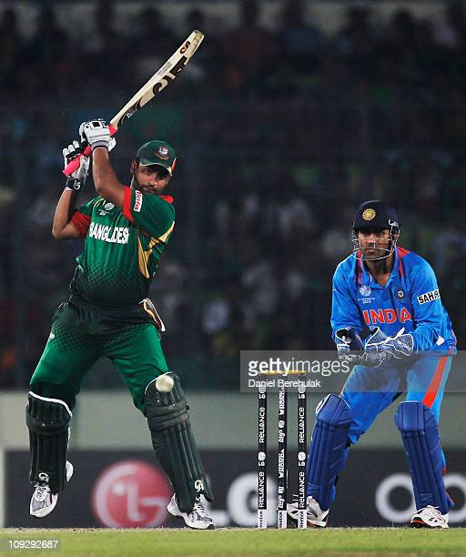 Tamim Iqbal of Bangladesh bats as captain MS Dhoni of India looks on during the opening game of the ICC Cricket World Cup between Bangladesh and...