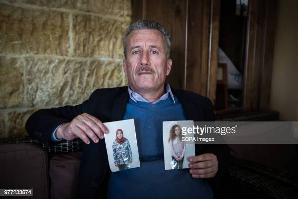 Tamimi's father holding two pictures in his home in Nabi Salih Ahed Tamimi has been in prison since December 2017 she is a teenage activist in...