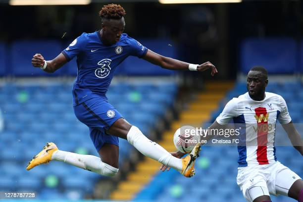 Tammy Abraham of Chelsea controls the ball in the air as Cheikhou Kouyate of Palace watches during the Premier League match between Chelsea and...