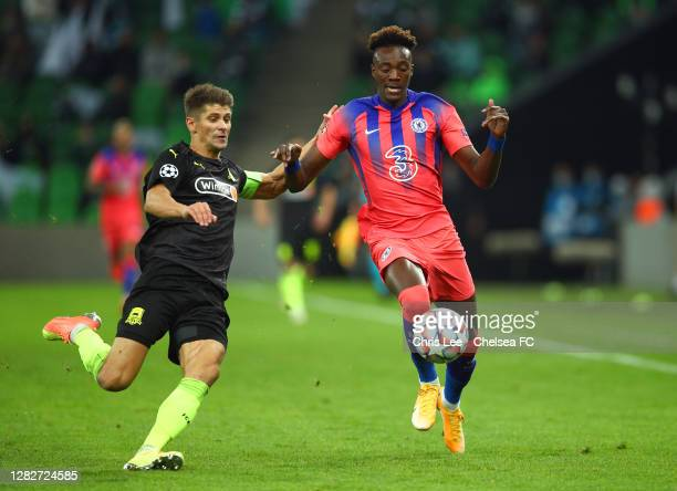 Tammy Abraham of Chelsea is challenged by Alyaksandr Martynovich of FC Krasnodar during the UEFA Champions League Group E stage match between FC...