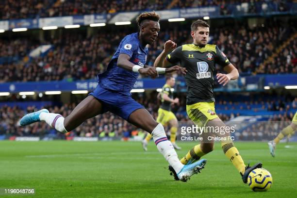 Tammy Abraham of Chelsea is challenged by Jack Stephens of Southampton during the Premier League match between Chelsea FC and Southampton FC at...