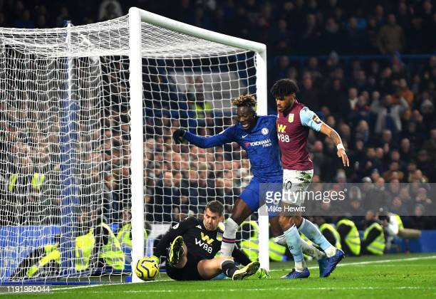 Tammy Abraham of Chelsea is stopped from scoring by Tom Heaton and Tyrone Mings of Aston Villa during the Premier League match between Chelsea FC and...