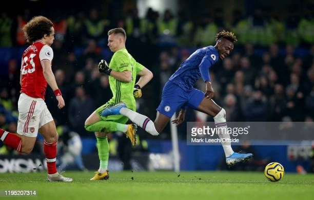 Tammy Abraham of Chelsea skips past Arsenal goalkeeper Bernd Leno with David Luiz of Arsenal in pursuit during the Premier League match between...