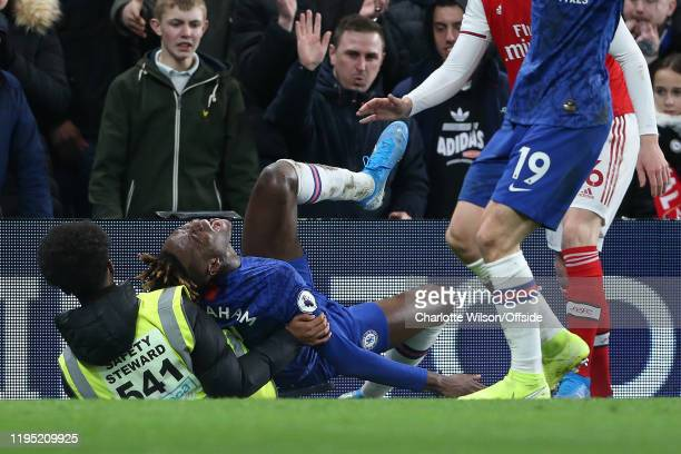 Tammy Abraham of Chelsea writhes in pain after colliding with a steward during the Premier League match between Chelsea FC and Arsenal FC at Stamford...