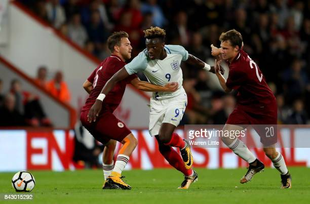 Tammy Abraham of England goes past Kriss Karklins and Eduards Emsis of Latvia during the UEFA Under 21 Championship Qualifiers between England and...