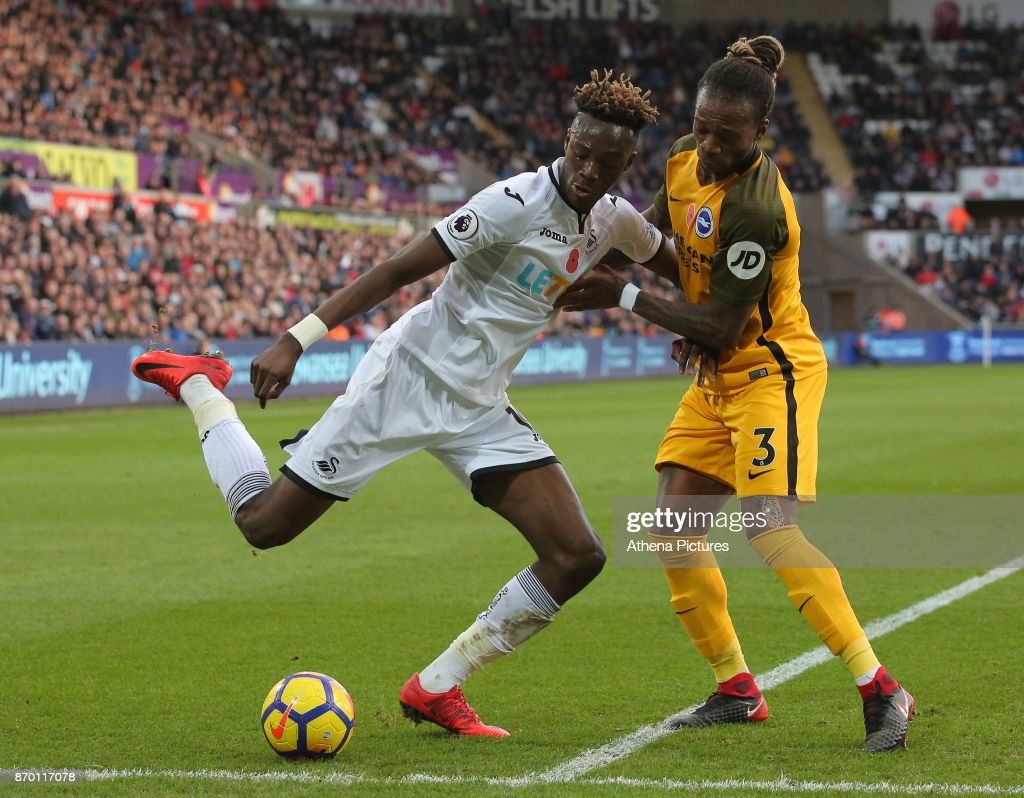 Tammy Abraham of Swansea City challenged by Gaetan Bong of Brighton during the Premier League match between Swansea City and Brighton and Hove Albion at The Liberty Stadium on November 04, 2017 in Swansea, Wales.