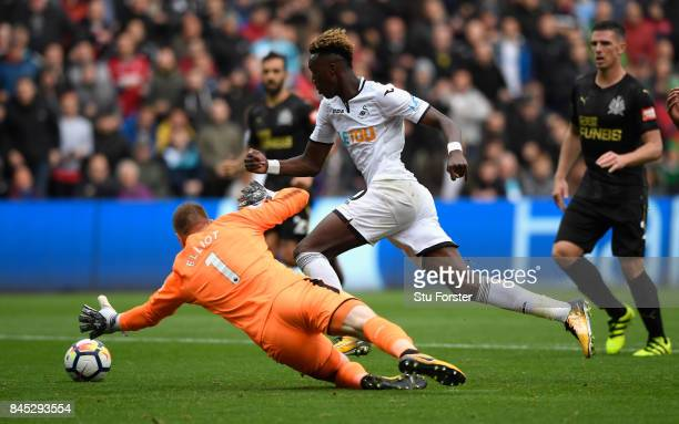 Tammy Abraham of Swansea City goes around Robert Elliot of Newcastle United during the Premier League match between Swansea City and Newcastle United...