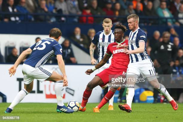 Tammy Abraham of Swansea City is challenged by Craig Dawson and Chris Brunt of West Bromwich Albion during the Premier League match between Swansea...