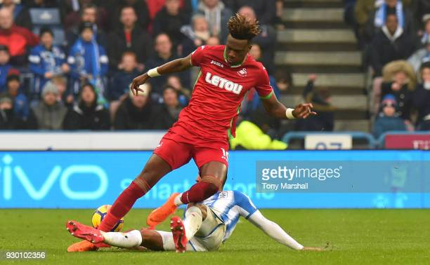 Tammy Abraham of Swansea City is tackled by Rajiv van La Parra of Huddersfield Town during the Premier League match between Huddersfield Town and...
