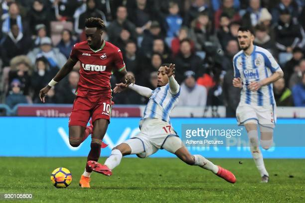 Tammy Abraham of Swansea City is tackled by Rajiv van La Parra of Huddersfield during the Premier League match between Huddersfield Town and Swansea...