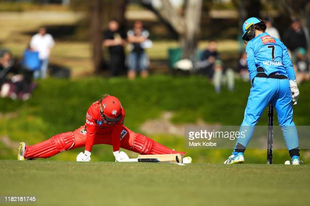 Tammy Beaumont of the Renegades stretches to make her ground as Tegan McPharlin of the Strikers watches on during the Women's Big Bash League match...