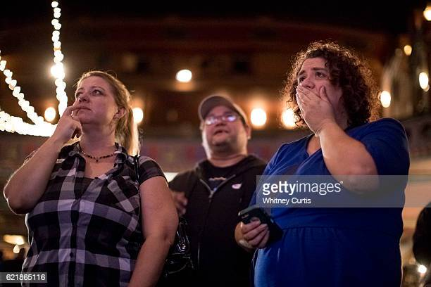 Tammy Wallace Ricardo Falciola and Allie Zaroor supporters of Jason Kander and Hillary Clinton watch poll returns at Uptown Theater on November 8...