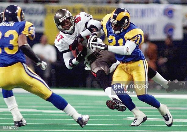 Tampa Bay Buccaneers Bert Emanuel comes down with the ball and is hit by St Louis Rams Dexter McCleon 23 January 2000 during the first half of the...
