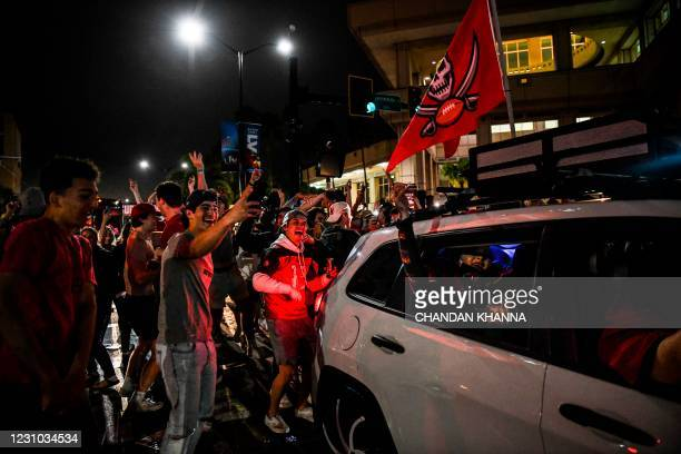 Tampa Bay Buccaneers fans celebrate their victory over the Kansas City Chiefs during Super Bowl LV in a street in downtown Tampa, Florida on February...