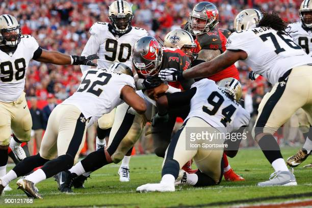 Tampa Bay Buccaneers quarterback Jameis Winston fights his way thru New Orleans Saints defensive end Cameron Jordan New Orleans Saints defensive...