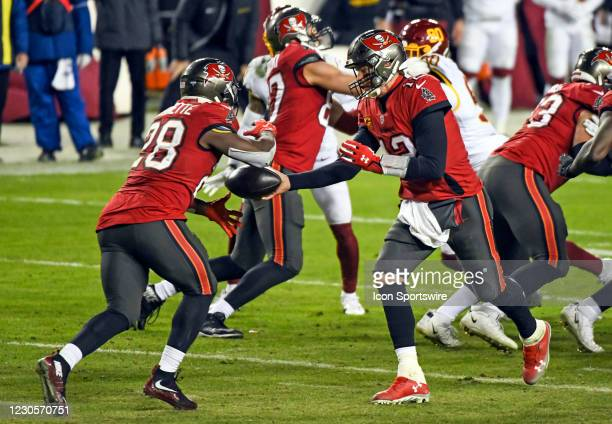 Tampa Bay Buccaneers quarterback Tom Brady hands the ball of to running back Leonard Fournette during the Tampa Bay Buccaneers Wild Card game versus...