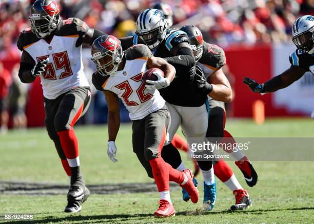 Tampa Bay Buccaneers running back Doug Martin is pursued by Carolina Panthers defensive tackle Vernon Butler during the first half of an NFL football...