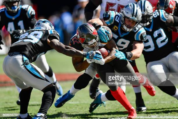 Tampa Bay Buccaneers running back Doug Martin is tackled by Carolina Panthers linebacker Luke Kuechly and Carolina Panthers safety Mike Adams during...