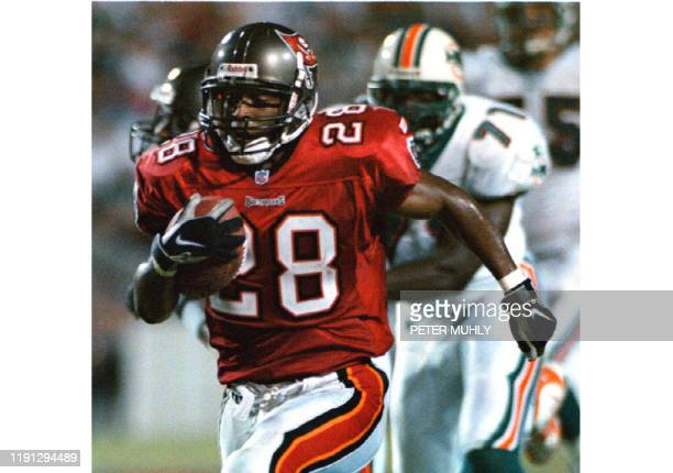 Tampa Bay Buccaneers Warrick Dunn runs for 58yards to score a touchdown on a reception from quarterback Trent Dilfer as a Miami Dolphins defender...